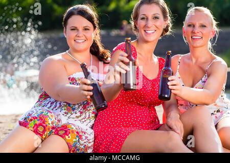 Les amis de boire une bière à river beach Banque D'Images