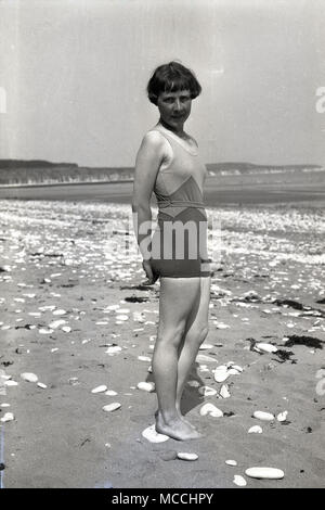 Années 1930, historiques, jeune femme de détente sur une plage portant un maillot une pièce de l'époque, Angleterre, Royaume-Uni. Banque D'Images