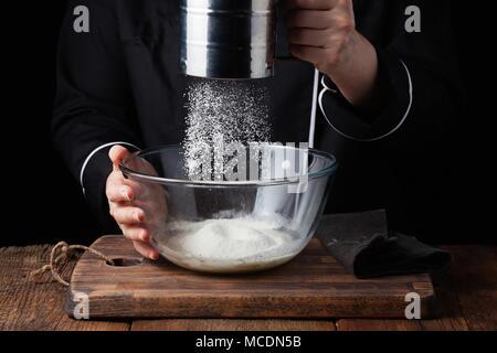 Verser la poudre de farine Chef mains sur la grille à l'aide de pâte crue sur un fond noir, processus de cuisson. Banque D'Images