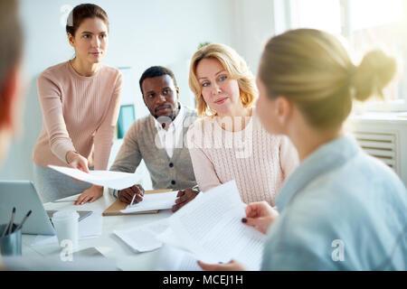 Young manager passant document à collègue blonde tout en ayant travailler réunion au grand open plan office Banque D'Images