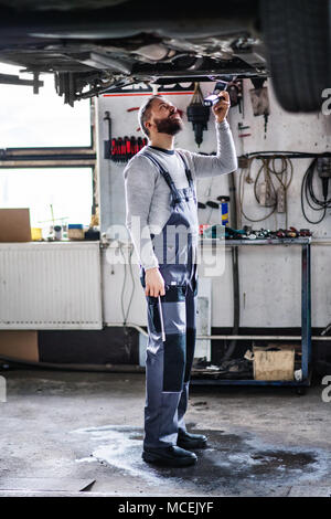Homme mechanic repairing une voiture dans un garage. Banque D'Images
