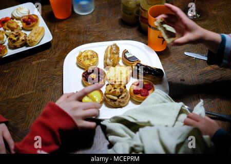Portrait d'une assiette de kid's cueillette manuelle mini frais et délicieux gâteaux et pâtisseries françaises au large de la plaque pendant une partie Banque D'Images