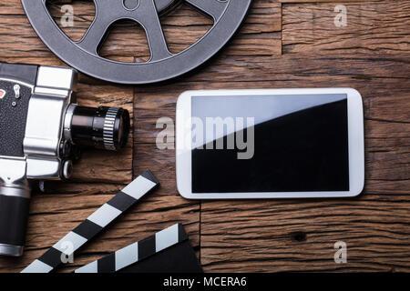 Portrait de Smartphone avec appareil photo et film bobine de film sur fond de bois Banque D'Images