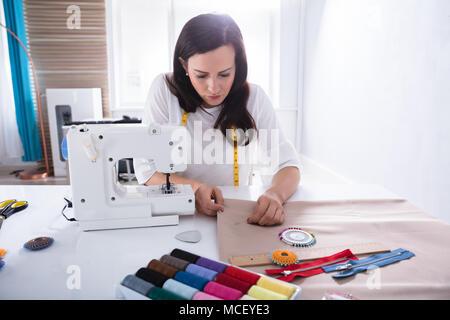 Jeune créateur de mode féminine Tissu Couture avec aiguille en Studio Banque D'Images