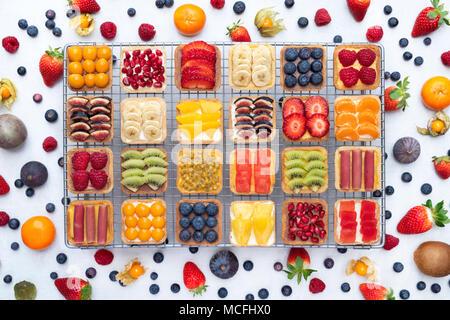 Tartes aux fruits carrés colorés sur une grille de refroidissement sur un fond blanc. Banque D'Images
