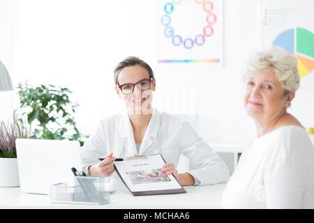 Diététiste dans les verres montrant un presse-papiers avec le plan de régime à l'avant à l'appareil photo Banque D'Images
