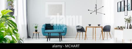 Deux tasses de café sur une table de bois blanc à l'intérieur salon avec canapé bleu et argent peinture sur le mur Banque D'Images