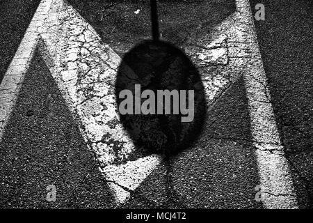 Plaque de rue de l'ombre sur la route d'asphalte, de l'arrière-plan.