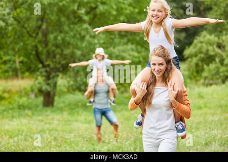 Happy kids ride sur le dos d'un voyage avec leurs parents Banque D'Images