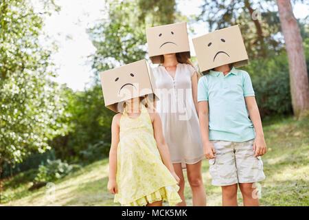 La famille anonyme se cache dans des boîtes de carton avec un chagrin face dans un jardin Banque D'Images