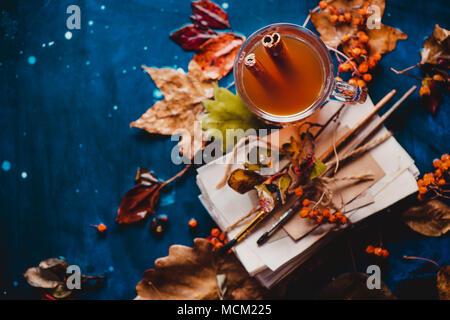 Mise à plat de l'automne avec les feuilles tombées et une pile d'artiste scetches avec brosses de peinture. La vie encore des pluies avec une tasse de thé en verre sur un background en bois humide Banque D'Images