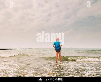 Les enfants sur la plage rendez-vous dans l'océan. Kid jouer dans les vagues de la mer mousseuse. Banque D'Images