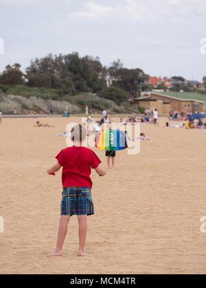 Deux petits garçons en premier plan un holding de contrôle à distance d'un autre cerf-volant multicolore et le lancement de cerf-volant tenant en l'air sur une plage magnifique. Banque D'Images