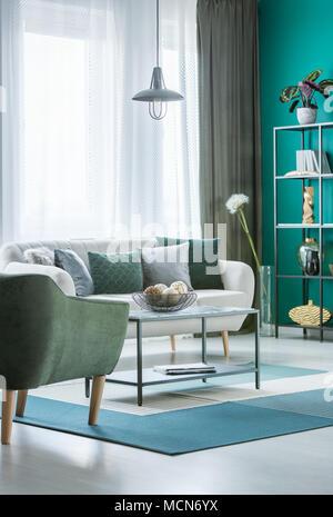 Table en métal avec boules décoratives dans un bol en vert intérieur salon avec canapé gris clair et des fenêtres avec des rideaux