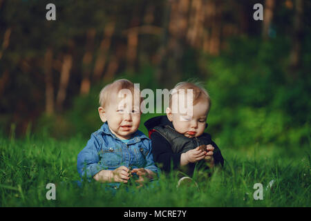 Deux jeunes garçons assis sur l'herbe dans le parc solaire d'été Banque D'Images