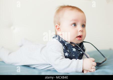 00904a03e57149 Peu drôle bébé garçon aux grands yeux bleus et des lunettes de soleil sur sa  tête