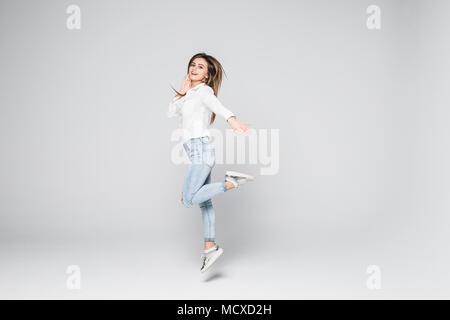 Portrait d'une belle jeune fille brune sautant et souriant heureusement isolé sur fond blanc Banque D'Images