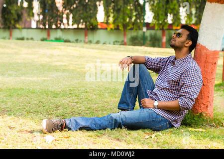 Jeune homme portant des lunettes de soleil et de détente leaning against tree Banque D'Images