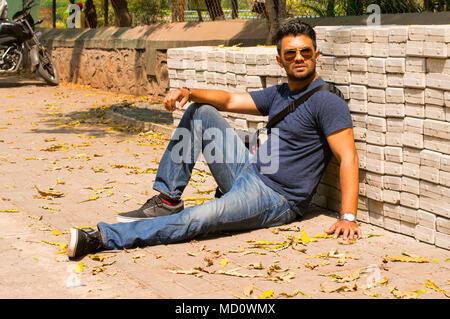 Jeune homme portant des jeans et t-shirt s'assied et pose Banque D'Images