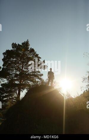 Silhouette d'été d'un homme au sommet d'une montagne, a atteint le sommet, a vaincu lui-même, la lumière du soleil de derrière, l'espace libre pour la signature. Réalisation, ove Banque D'Images