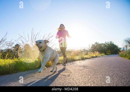 Jeune femme tournant le long chemin rural avec chien de compagnie, low angle view Banque D'Images