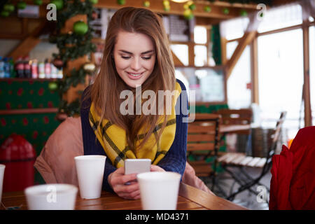 Young woman smiling over text message on mobile phone Banque D'Images