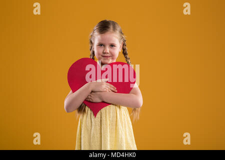 Portrait avant d'happy young girl holding big red heart Banque D'Images