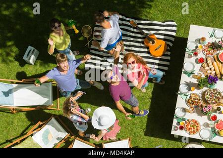 Heureux les jeunes gens se détendre et jouer au badminton à un barbecue dans le jardin Banque D'Images
