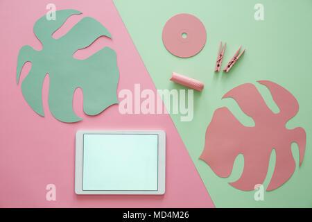 Feuille rose sur fond vert et copiez l'espace sur une tablette avec cadre blanc