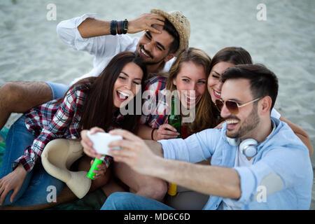 Des amis ayant un grand temps à la plage Banque D'Images