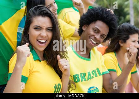 Groupe d'acclamations brazilian soccer fans avec drapeau du Brésil soutenir l'équipe nationale à stade Banque D'Images