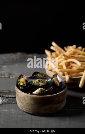 Moules-frites, des moules et des frites typique de la Belgique, sur une table en bois rustique, d'un fond noir, avec un peu d'espace vide en haut