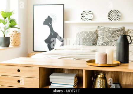 Close-up d'une armoire en bois avec des bougies d'intérieur dans une chambre à coucher avec lit double et d'un graphique à l'arrière-plan Banque D'Images
