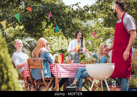 Groupe d'amis gais et de faire la fête ensemble de cuisson dans le jardin Banque D'Images