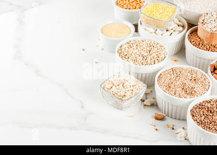 Différents types de sélection de céréales Gruaux dans différents bol sur fond de marbre blanc, de l'espace pour le texte Banque D'Images
