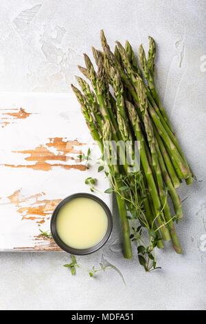 Les asperges vertes fraîches et vieille planche de bois blanc