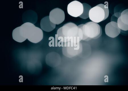 Résumé arrière-plan flou. Taches de lumière Monochrome sur fond sombre. Banque D'Images