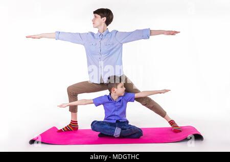 Mère et fils faisant du yoga, dépenser un bon temps ensemble . isolé sur blanc. Banque D'Images