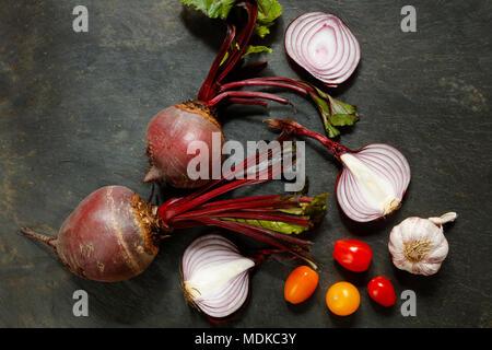 Betterave rouge frais entier avec oignons, ail et tomates cerise sur le tableau en ardoise avec copie espace Banque D'Images