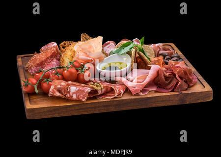 Plaque de savoureux fromage, salami, prosciutto, tomates cerises sur planche de bois Banque D'Images