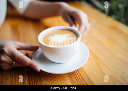 Close up of female hands holding tasse de boisson chaude dans la cafétéria Banque D'Images