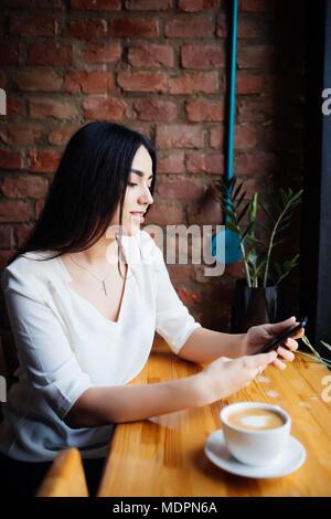 Portrait of young businesswoman utilisation téléphone mobile tout en restant assis dans un café confortable pause pendant le travail Banque D'Images