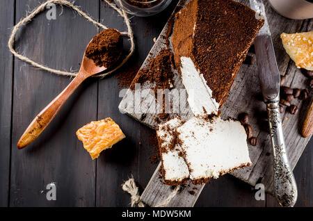 Fromage maison douce enveloppée dans du café moulu et une tasse de café avec du lait petit-déjeuner sur une table en bois Banque D'Images
