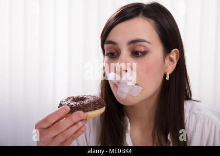 Close-up of a young woman avec du ruban gommé sur la bouche incapable de manger Donut Banque D'Images