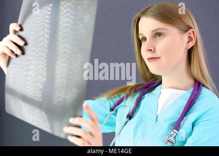 Femme médecin à la recherche de X-ray photo. De couleur uniforme en vert. Purple stéthoscope. Les soins de santé, l'assurance et medicine concept Banque D'Images