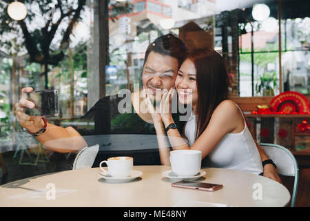 Jolie asian couple having coffee Banque D'Images