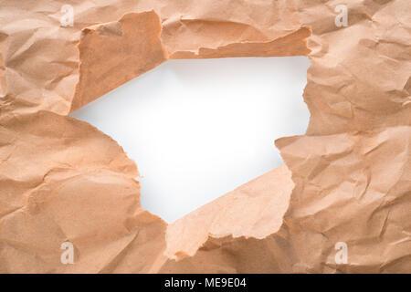 Trou dans le papier kraft brun feuille avec bords déchirés. Centre blanc isolé, chemin de détourage inclus