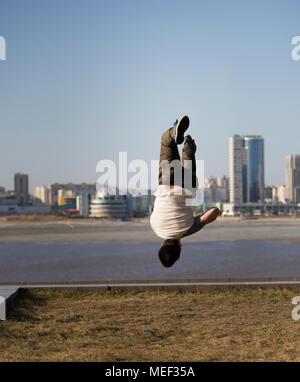 Jeune homme sportif acrobatique effectue tricks à l'envers en face de Skyline Banque D'Images