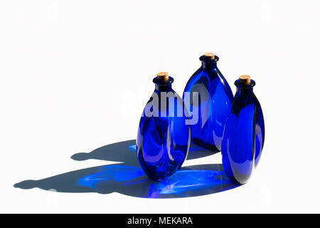 L'eau solaire bleue en bleu les bouteilles de verre scellé avec les bouchons en liège. Isolé sur fond blanc. Banque D'Images