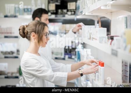 Les pharmaciens travaillant dans le magasin de la pharmacie Banque D'Images